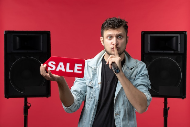 붉은 벽에 판매 쓰기를 들고 무대에서 수행하는 남성 가수의 전면보기