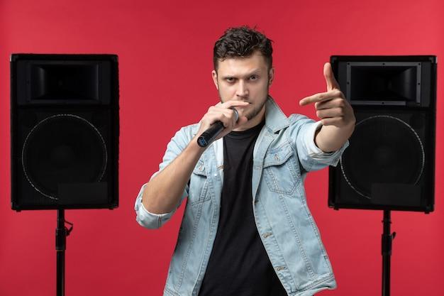 Вид спереди певца, выступающего на сцене с микрофоном на красной стене