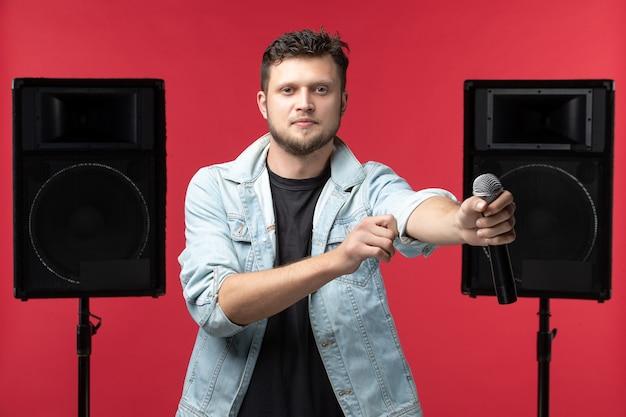 붉은 벽에 마이크와 함께 무대에서 공연하는 남성 가수의 전면보기