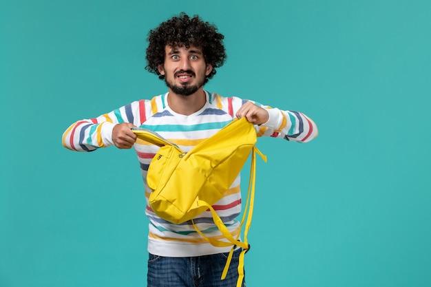 青い壁に黄色のバックパックを保持している男子学生の正面図