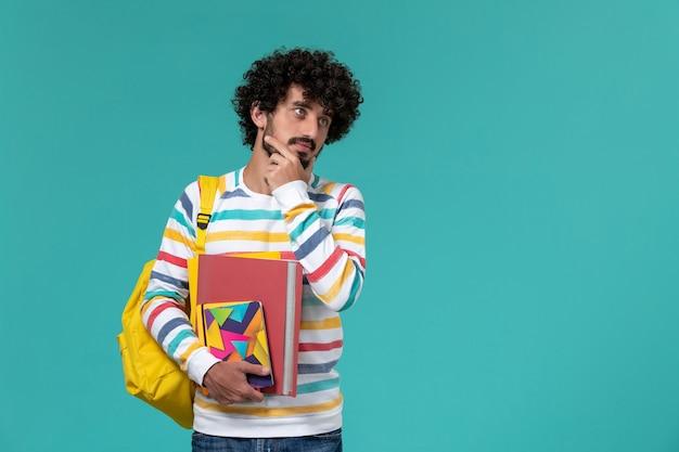 Вид спереди студента в цветной полосатой рубашке в желтом рюкзаке с файлами и тетрадями, думающего на синей стене