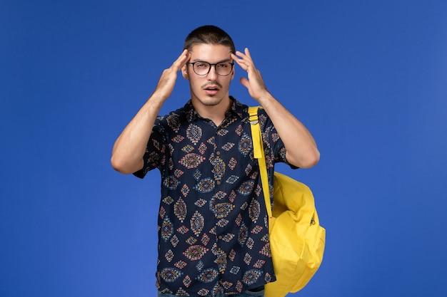 青い壁に黄色のバックパックを身に着けている暗い綿のシャツを着た男子学生の正面図