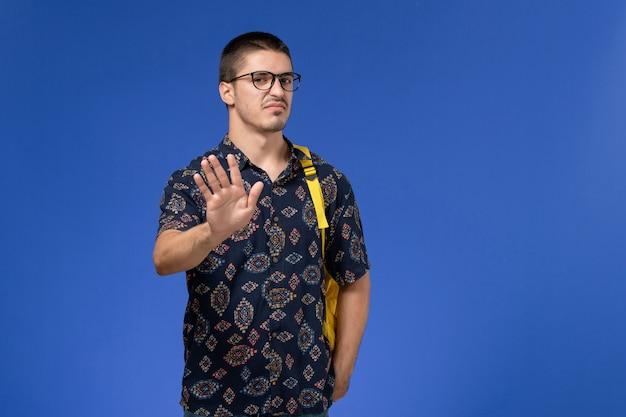 Студент в темной хлопковой рубашке, одетый в желтый рюкзак, позирует на синей стене, вид спереди