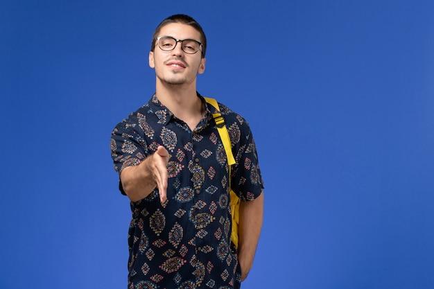 青い壁に手を振って黄色のバックパックを身に着けている暗い綿のシャツの男子学生の正面図