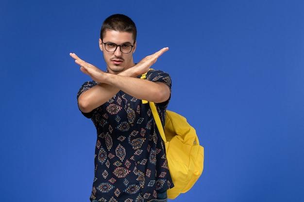 파란색 벽에 금지 기호를 보여주는 노란색 배낭을 입고 어두운 면화 셔츠에 남성 학생의 전면보기