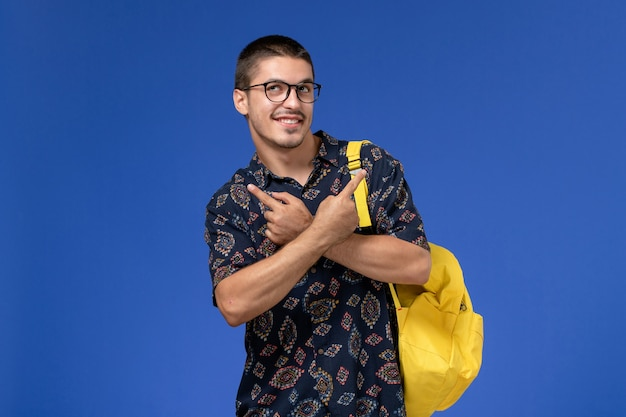 Студент в темной хлопковой рубашке, одетый в желтый рюкзак, улыбается на синей стене, вид спереди