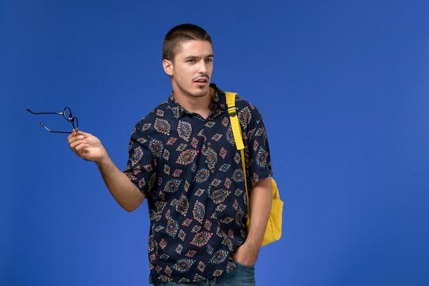 파란색 벽에 그의 광학 선글라스를 벗고 노란색 배낭을 착용하는 어두운 면화 셔츠에 남성 학생의 전면보기