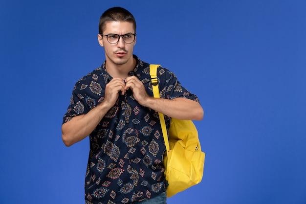 黄色のバックパックを身に着けている暗い綿のシャツを着た男子学生の正面図