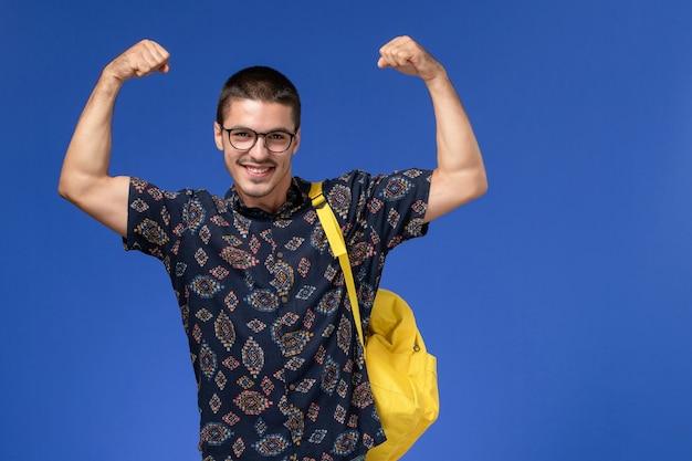 青い壁に曲がる黄色のバックパックを身に着けている暗いシャツを着た男子学生の正面図