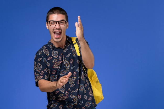Студент в темной рубашке, одетый в желтый рюкзак, громко смеется на голубой стене, вид спереди