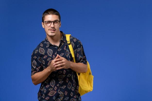 파란색 벽에 노란색 배낭을 입고 어두운 셔츠에 남성 학생의 전면보기