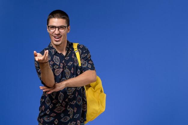 青い壁に黄色のバックパックを身に着けている暗いシャツを着た男子学生の正面図