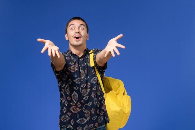 黄色のバックパックを身に着けている暗いシャツの男子学生の正面図