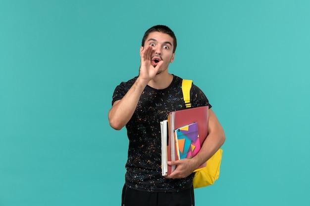 Студент в темной футболке с желтым рюкзаком, держащий тетрадь и файлы, выкрикивающий на синей стене, вид спереди