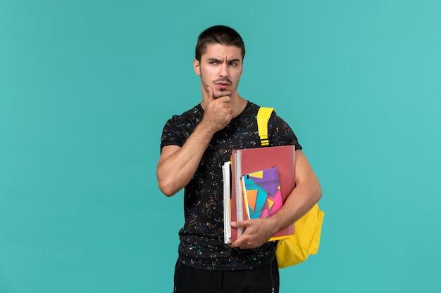 파란색 벽에 생각 카피 북 및 파일을 들고 노란색 배낭을 입고 어두운 티셔츠에 남성 학생의 전면보기