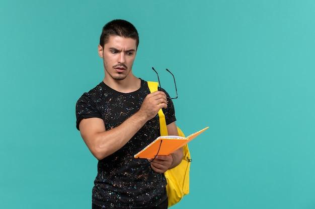 Вид спереди студента в темной футболке с желтым рюкзаком, держащего и читающего тетрадь на синей стене