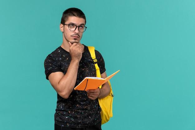 Вид спереди студента в темной футболке с желтым рюкзаком, держащего и читающего тетрадь, думая на синей стене