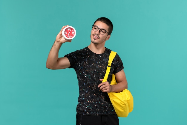 파란색 벽에 시계를 들고 어두운 티셔츠 노란색 배낭에 남성 학생의 전면보기