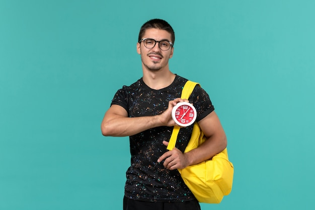 青い壁に時計を保持している暗いtシャツ黄色のバックパックの男子学生の正面図