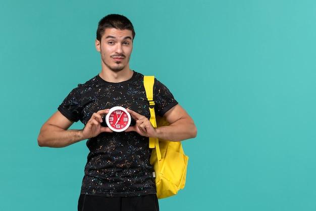 水色の壁に時計を保持している暗いtシャツ黄色のバックパックの男子学生の正面図