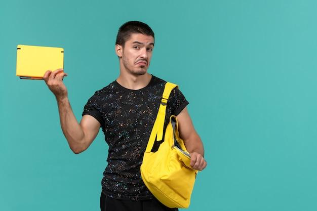 水色の壁にコピーブックを保持している暗いtシャツ黄色のバックパックの男子学生の正面図