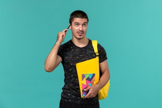 밝은 파란색 벽에 생각 카피 북 펜 및 파일을 들고 어두운 티셔츠 노란색 배낭에 남성 학생의 전면보기