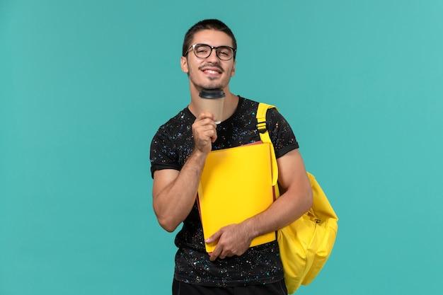 Вид спереди студента в темной футболке, желтом рюкзаке с разными файлами и кофе на синей стене