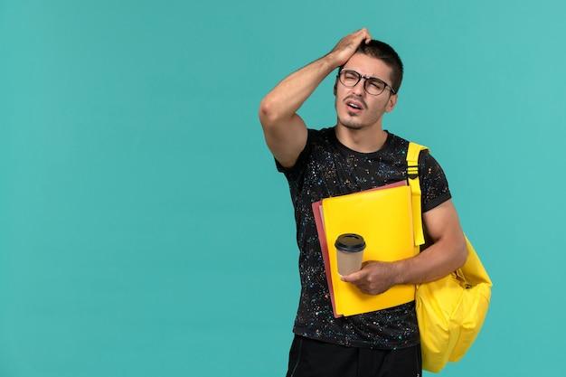 Вид спереди студента в темной футболке с желтым рюкзаком, держащего разные файлы и кофе, думающего на синей стене