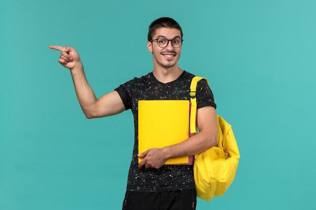 Студент в темной футболке с желтым рюкзаком, держащий разные файлы на голубой стене, вид спереди