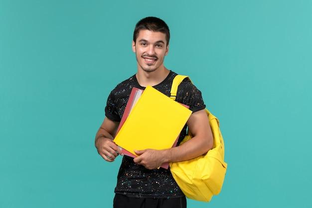 水色の壁にさまざまなファイルを保持している暗いtシャツ黄色のバックパックの男子学生の正面図