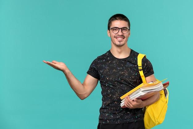 Студент в темной футболке с желтым рюкзаком, держащий файлы и книги, улыбается на голубой стене, вид спереди