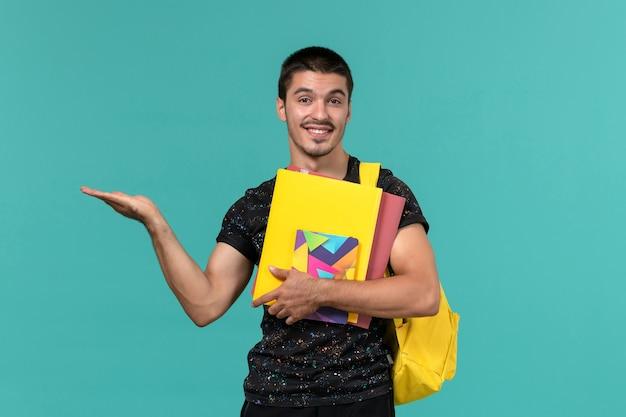 밝은 파란색 벽에 파일 및 카피 북을 들고 어두운 티셔츠 노란색 배낭에 남성 학생의 전면보기