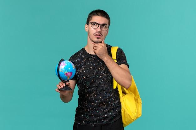 Вид спереди студента в темной футболке с желтым рюкзаком, держащего маленький глобус и думающего на синей стене