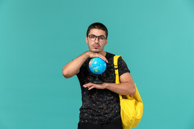 青い壁に小さな地球を保持している暗いtシャツ黄色のバックパックで男子学生の正面図