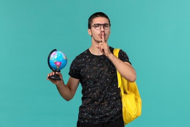 Студент в темной футболке с желтым рюкзаком, держащий глобус на синей стене, вид спереди