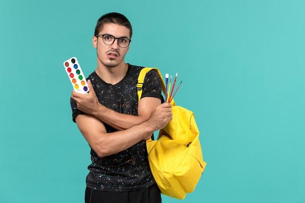 밝은 파란색 벽에 페인트와 술을 들고 어두운 티셔츠 노란색 배낭에 남성 학생의 전면보기