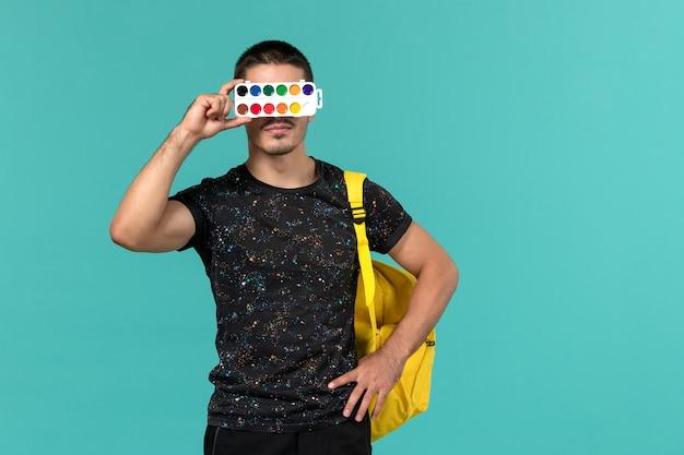 파란색 벽에 페인트를 들고 어두운 티셔츠 노란색 배낭 남성 학생의 전면보기