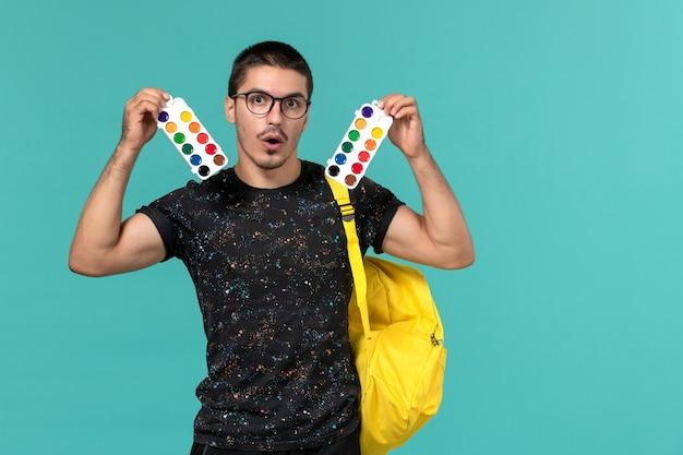 밝은 파란색 벽에 페인트를 들고 어두운 티셔츠 노란색 배낭에 남성 학생의 전면보기