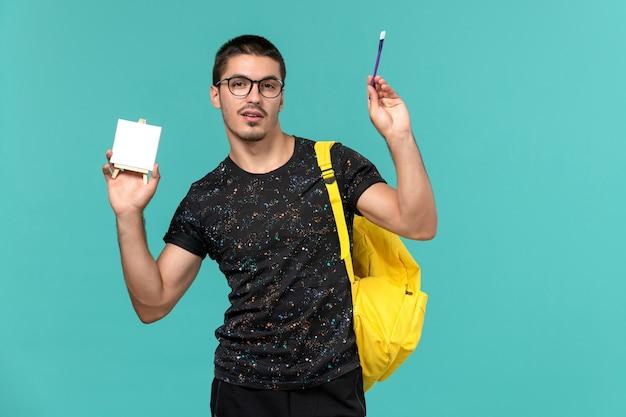 밝은 파란색 벽에 술과 이젤을 들고 어두운 티셔츠 노란색 배낭에 남성 학생의 전면보기