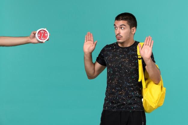 水色の壁の時計を見ている暗いtシャツ黄色のバックパックで男子学生の正面図