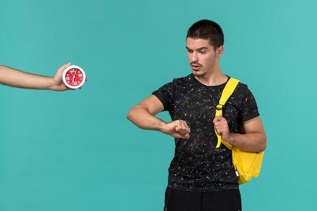 水色の壁に彼の手首を見ている暗いtシャツ黄色のバックパックで男子学生の正面図