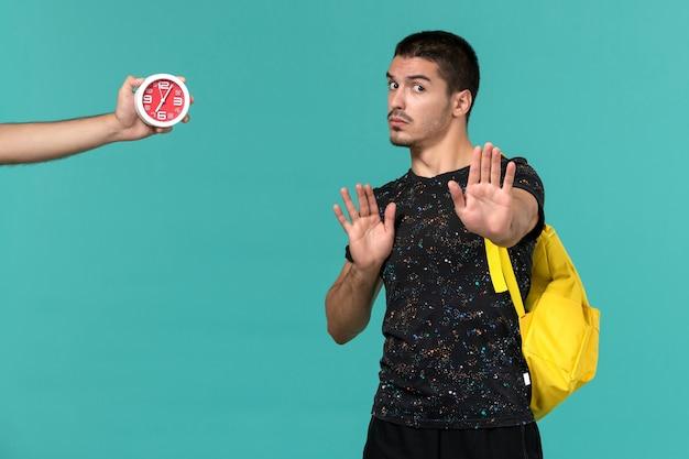 밝은 파란색 벽에 어두운 티셔츠 노란색 배낭에 남성 학생의 전면보기