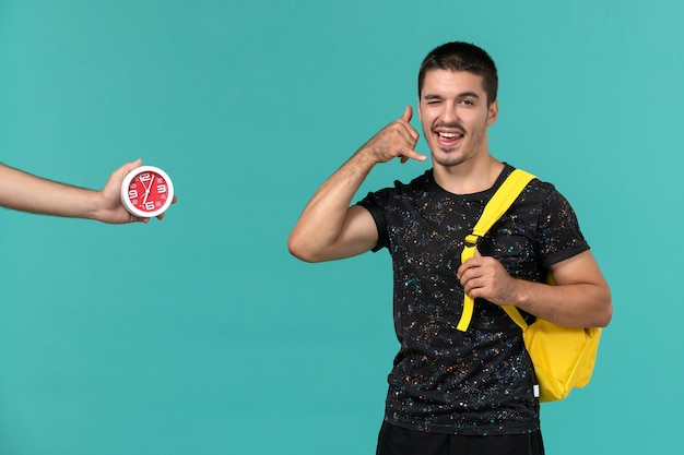 밝은 파란색 벽에 포즈를 취하는 어두운 티셔츠 노란색 배낭 남성 학생의 전면보기
