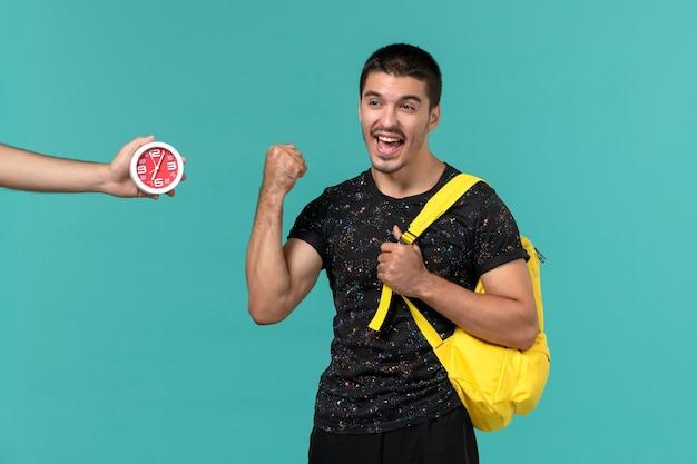 水色の壁に喜んで暗いtシャツ黄色のバックパックで男子学生の正面図