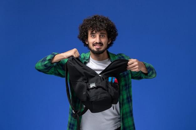 밝은 파란색 벽에 검은 가방을 들고 녹색 체크 무늬 셔츠에 남성 학생의 전면보기