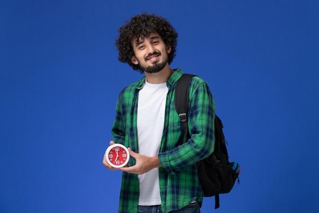 黒のバックパックを身に着け、青い壁に時計を保持している緑の市松模様のシャツの男子学生の正面図