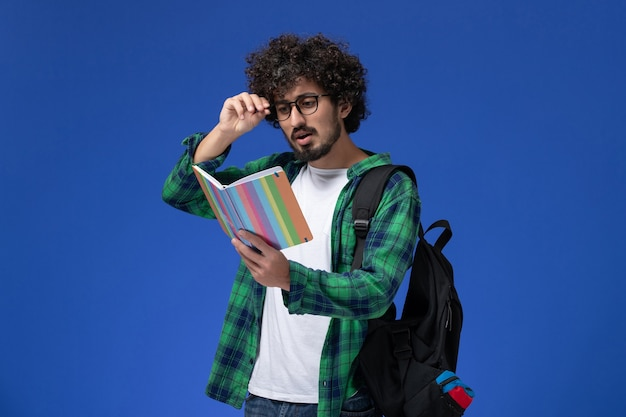 黒のバックパックを身に着けていると青い壁に法帖読書を保持している緑の市松模様のシャツの男子学生の正面図