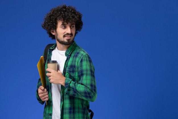 黒のバックパックを身に着けて、ファイルとコーヒーを保持している緑の市松模様のシャツの男子学生の正面図