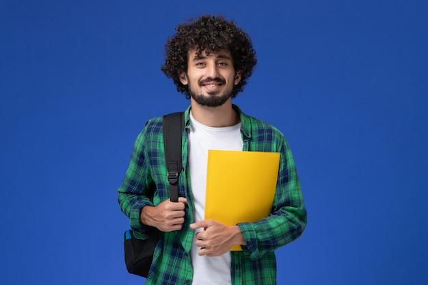 黒のバックパックを身に着けていると青い壁にファイルを保持している緑の市松模様のシャツの男子学生の正面図