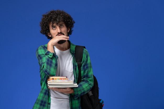 青い壁にコピーブックとファイルを保持している黒いバックパックと緑の市松模様のシャツの男子学生の正面図